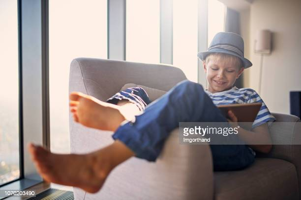 little boy enjoying playing games on tablet - lazy poland stock photos and pictures