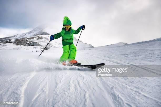 petit garçon appréciant skier au glacier dans les alpes - ski photos et images de collection