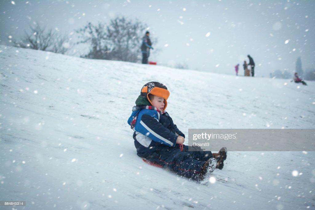 少し少年楽しんでそりに乗って雪の中に. : ストックフォト