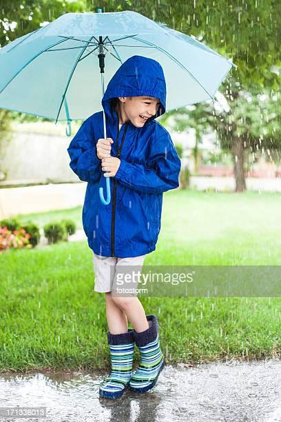 Kleine Junge Genießen Sie Sommer-Regen