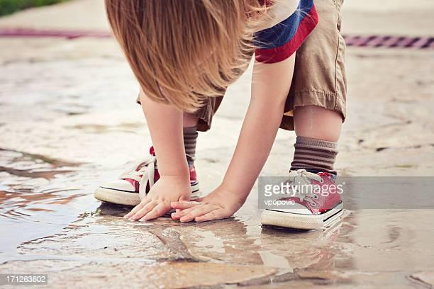 Little boy enjoying the summer rain puddle