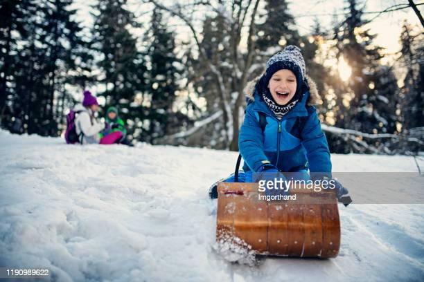 little boy enjoying tobogganing on winter day - tobogganing stock pictures, royalty-free photos & images