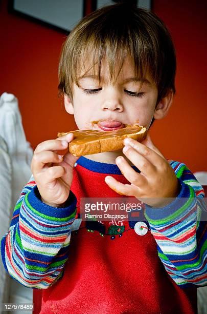 Little boy enjoying tost with dulce de leche