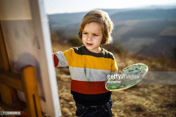 kleiner junge beim malen im herbst tag im freien zu genießen. - staffelei stock-fotos und bilder