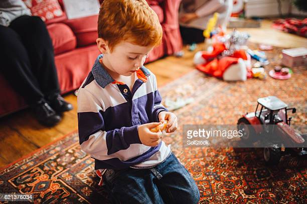 Little Boy Enjoys a Tangerine on Christmas Day