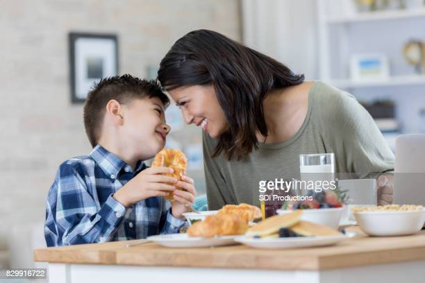 little boy enjoys breakfast with his mom - filipino family eating stock pictures, royalty-free photos & images