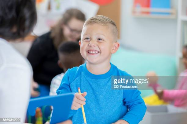 Little boy enjoys discussion with day care worker