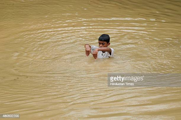 A little boy enjoys in logged water at a farming land after rains on July 12 2015 in Noida India Monsoon rains lashed Delhi for the fifth consecutive...