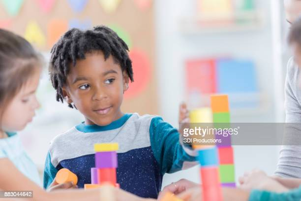 Little boy enjoys playing with building blocks at school