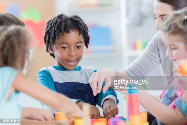 Little boy enjoys playing with friends and teacher at school