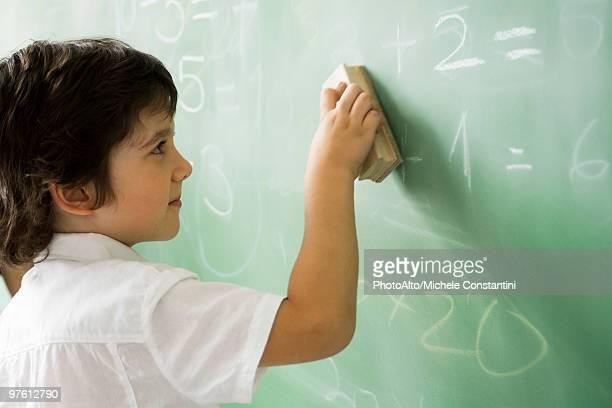 Little boy erasing classroom blackboard