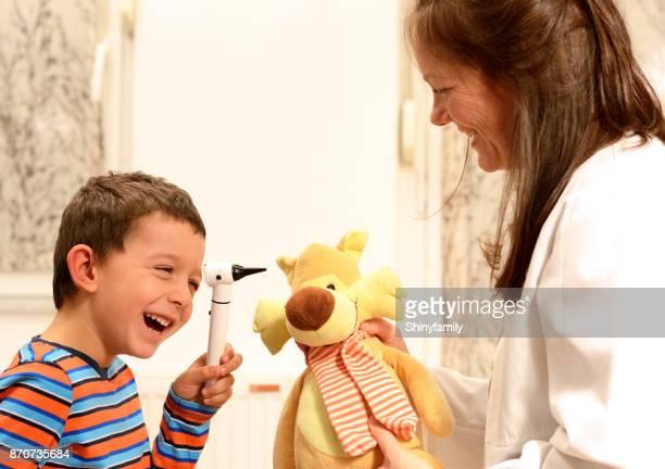 Little boy examining a stuffed toy using otoscope