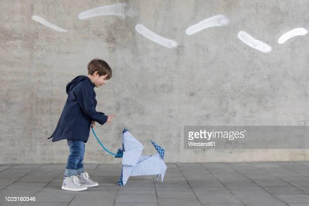 Little boy exercising with origami dog