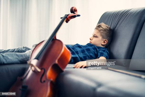 little boy exhausted by practicing cello - only boys stock pictures, royalty-free photos & images