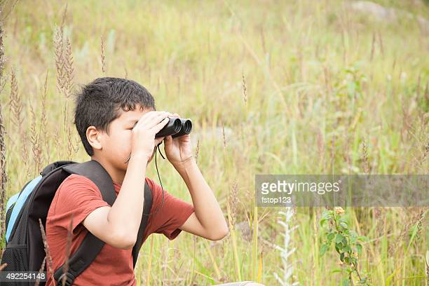 Little boy explores outdoors, nature using binoculars.  Meadow.  Summer.