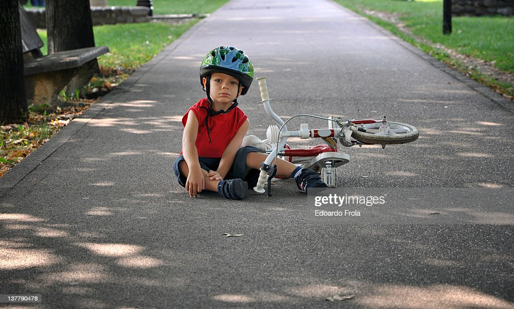 Little boy falling off bicycle : Foto stock