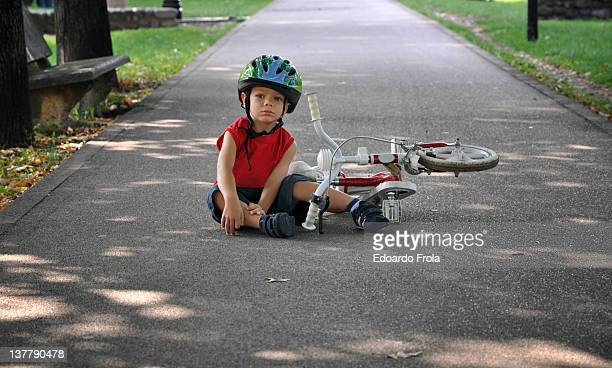 Little boy falling off bicycle
