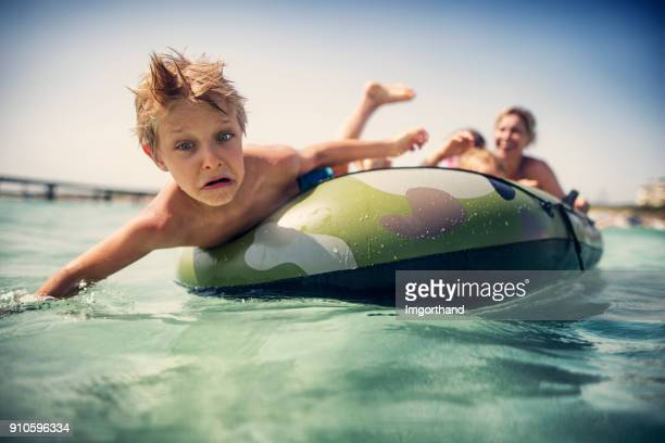 Little boy falling off inflatable boat