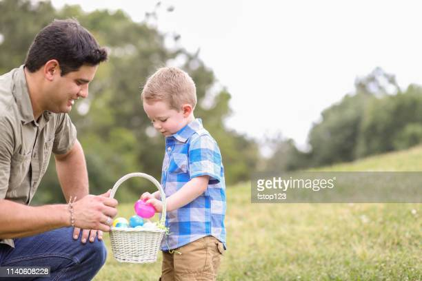 little boy, father hunting easter eggs at park. - easter egg hunt stock pictures, royalty-free photos & images