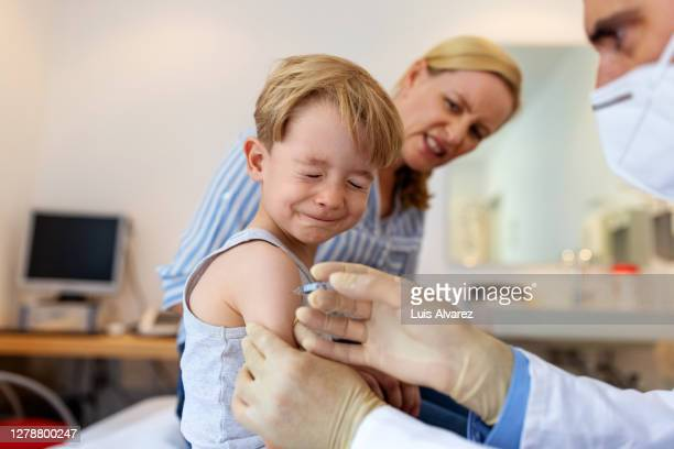 little boy feeling pain while getting a vaccine - impfung stock-fotos und bilder
