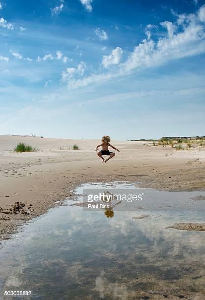 Little boy figure reflection in pool , Raabjerg Mile, Skagen, Denmark