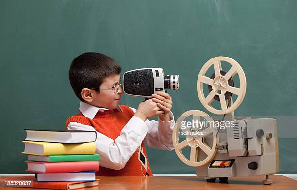 Little Boy Filming With Video Camera In Front Of Blackboard