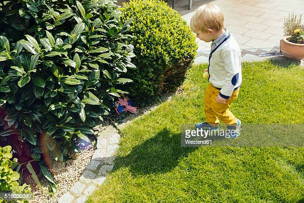 Little boy finding an Easter surprise in the garden