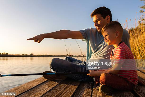 Little boy fishing with his father on a pier.