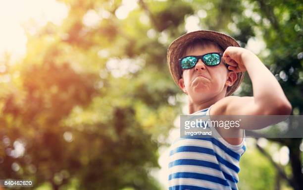 little boy flexing muscles in the park - flexing muscles stock pictures, royalty-free photos & images