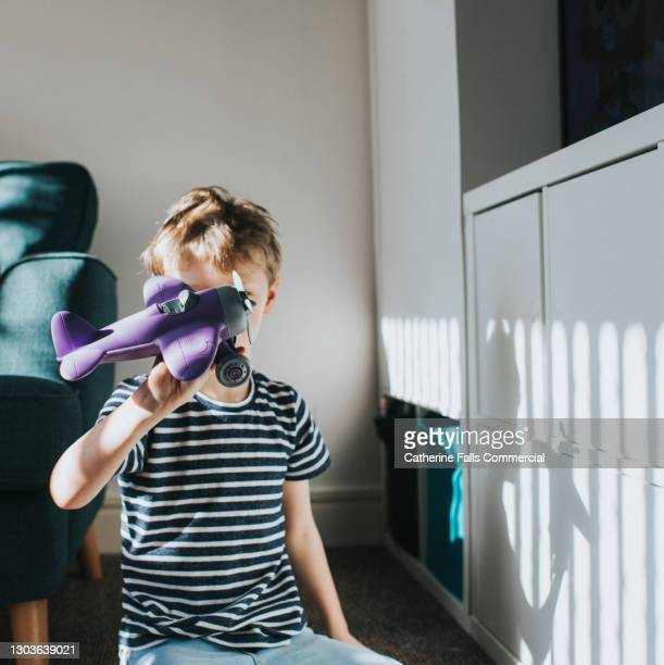 little boy flies a purple toy plane - air vehicle stock pictures, royalty-free photos & images