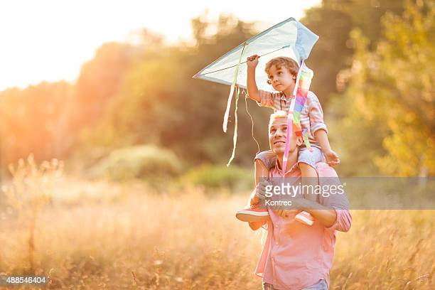 Little boy flying a kite with his father