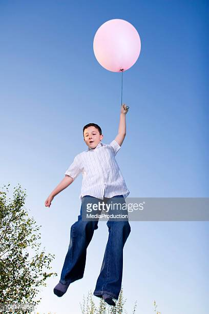 Petit garçon volant ballon avec rose
