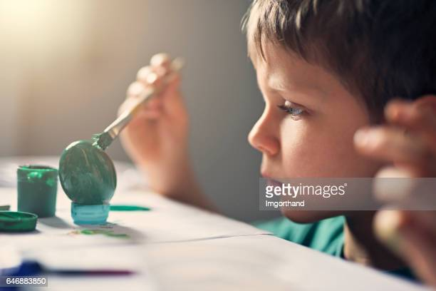 Little boy focused on painting easter egg