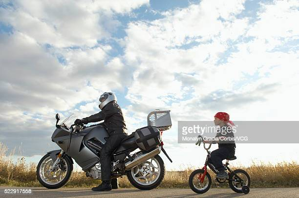 Little boy following motorcyclist on his bike