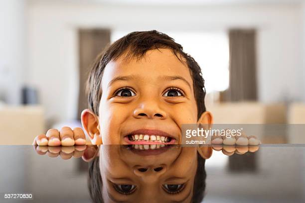 little boy fooling around at the kitchen counter - muslim boy stock photos and pictures