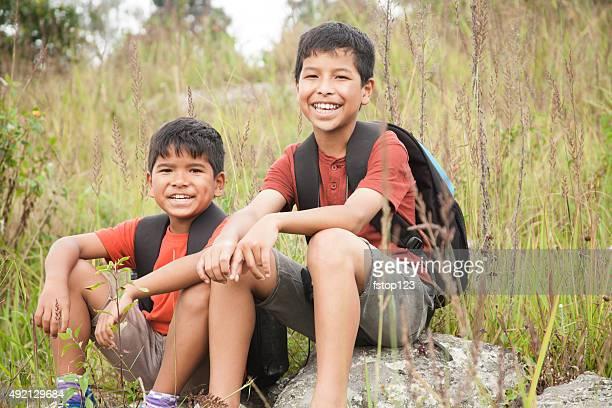 Little boy friends explore outdoors, nature. Backpacks. Meadow.  Summer.
