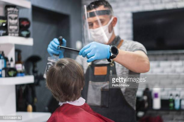 little boy getting haircut at the barbershop - hairstyle stock pictures, royalty-free photos & images