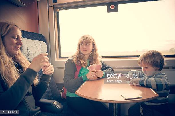 Little boy (3), girl (13) and mother playing cards in a train.