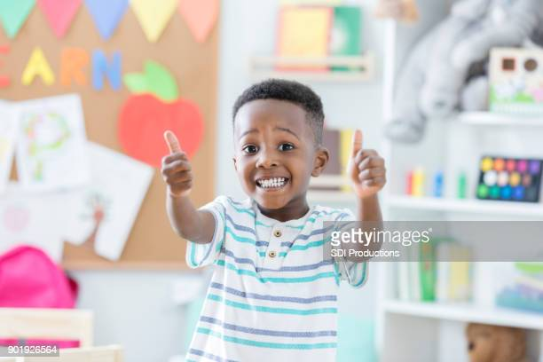 little boy gives new day care center two thumbs up - first day of school stock pictures, royalty-free photos & images