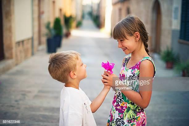 Little boy giving flower to smiling little girl.