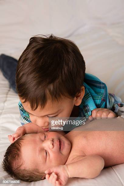 Little Boy Giving Kiss to Newborn Baby Brother