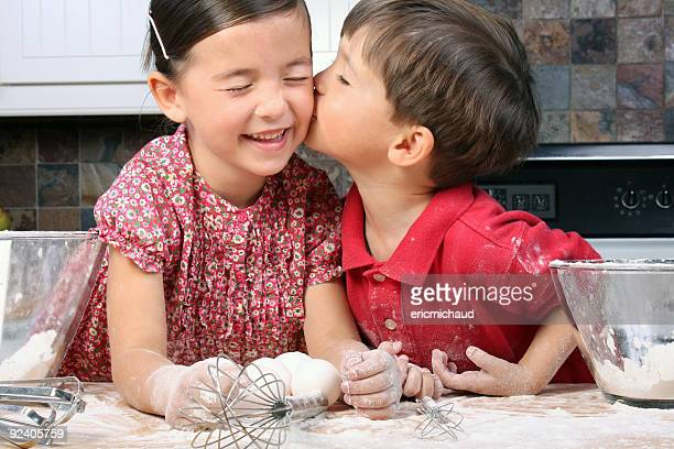Little boy giving little smiling girl a kiss on the cheek