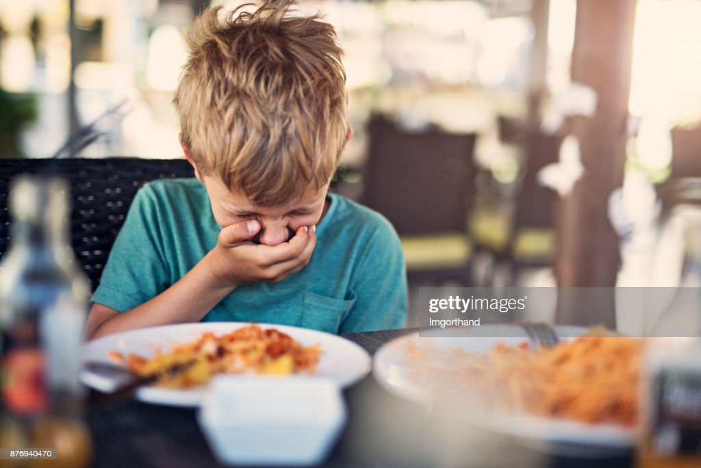 Little boy going to be sick in restaurant : Stock Photo