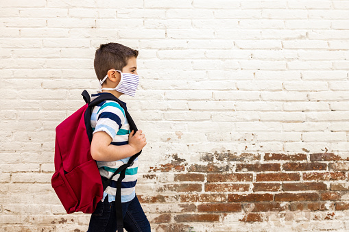 Little boy going to school with protective mask 1223794147