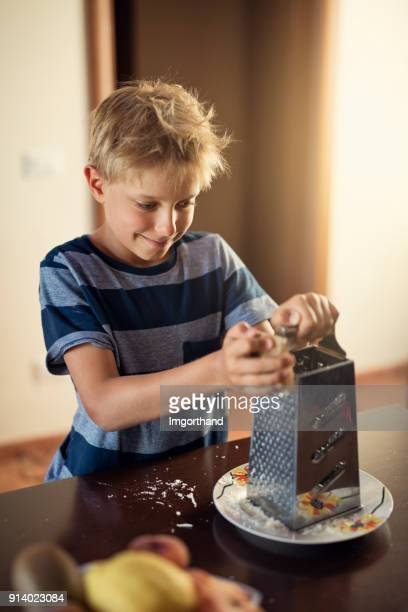 Little boy grating cheese for spaghetti