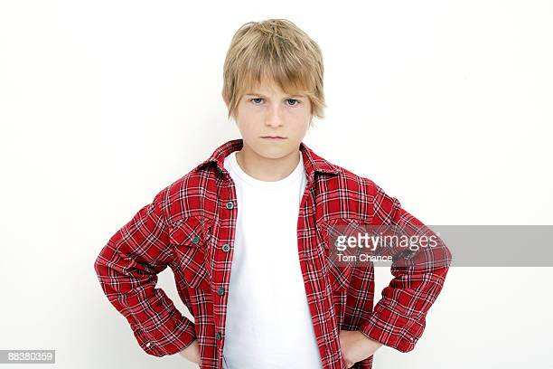Boy (10-11) standing with hands on hips, portrait, close-up
