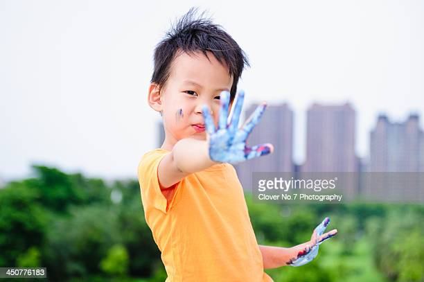 Little boy hands stained with watercolor.