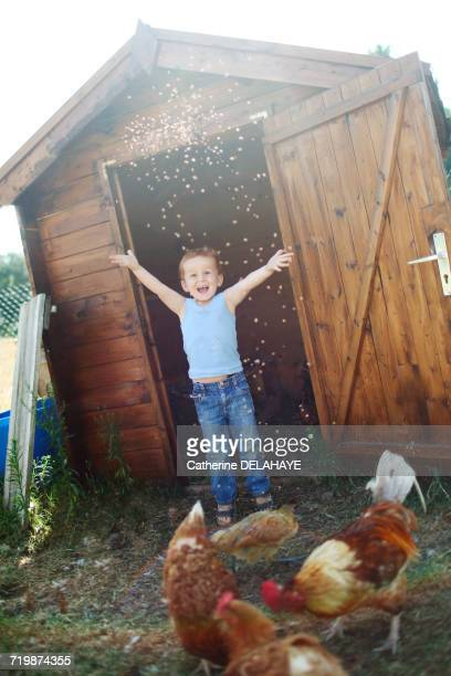 Little boy happily throwing seeds to the chickens in front of a henhouse