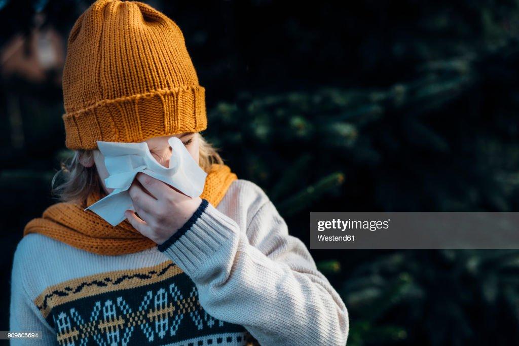 Little boy having a cold, blowing his nose : Foto de stock