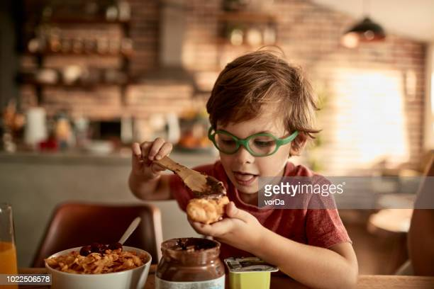 little boy having breakfast - nutella stock pictures, royalty-free photos & images